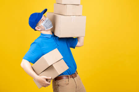 Delivery handsome man wearing mask with heavy many carton box picking up the package to front home receiver shipping deliver cargo prevention infected virus on yellow background isolated studio shot. Banque d'images