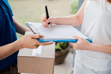 Door to door delivery express sending send a package wearing mask to customer receiver sign checking shipping deliver cargo prevention infection quarantine while the virus is spreading, Coronavirus. Banque d'images