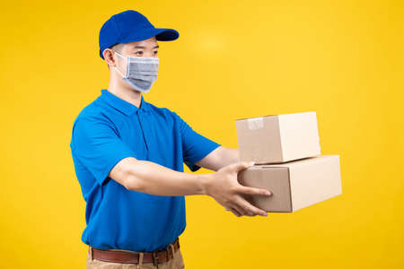 Delivery handsome man wearing mask with carton box picking up the package to front home receiver shipping deliver cargo prevention infected virus on yellow background isolated studio shot. Banque d'images
