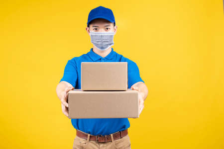 Delivery handsome man wearing and pointing mask with carton box picking up the package to front home receiver shipping deliver cargo prevention infected virus on yellow background isolated studio shot