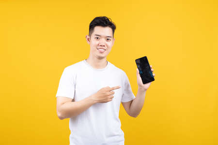 Attractive portrait happy young asian man showing mobile phone smiling at camera with copy space wearing white t-shirt on yellow background isolated studio shot.