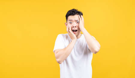 Attractive portrait happy young asian man excited wow emotion advertising promotion looking at camera with copy space wearing white t-shirt on yellow background isolated studio shot.
