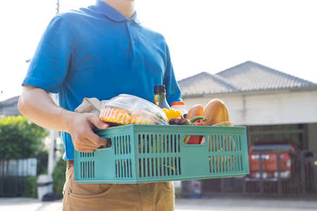 Food Deliver Asian man in blue uniform give fruit and vegetable to receiver customer front house, fast express grocery service when crisis coronavirus, new normal lifestyle concept.
