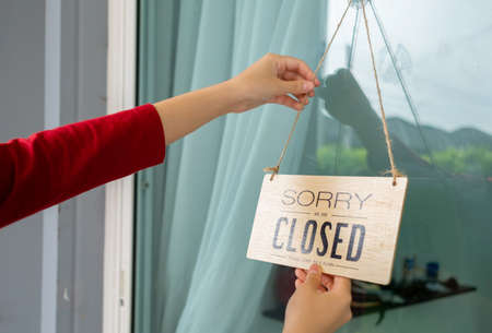 Woman closed store with sign board front door shop, Small business come back turning agian after the situation is resolved. Stock Photo