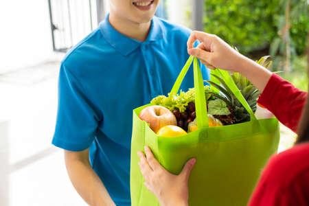 Essen liefern Asiatischer Mann in blauer Uniform gibt Obst und Gemüse an das Vorderhaus des Empfängers, schnellen Express-Lebensmittelservice bei Krisen-Coronavirus, Covid19 neues normales Lifestyle-Konzept.