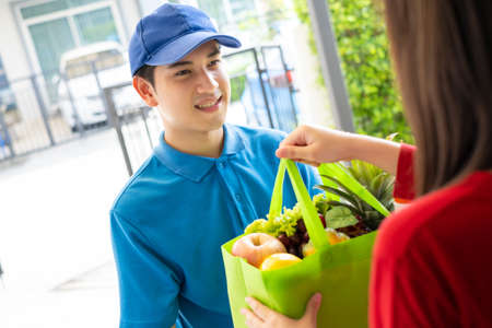 Food Deliver Asian man in blue uniform give fruit and vegetable to receiver customer front house, fast express grocery service when crisis coronavirus, covid19 new normal lifestyle concept. Archivio Fotografico
