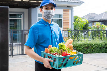 Food Deliver Asian man wearing mask in uniform give fruit and vegetable to receiver customer front house, fast express grocery service when crisis coronavirus, covid19 new normal lifestyle.