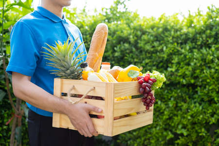 Food Deliver Asian man in blue uniform give fruit and vegetable to receiver customer front house, fast express grocery service when crisis coronavirus, new normal lifestyle concept. Reklamní fotografie