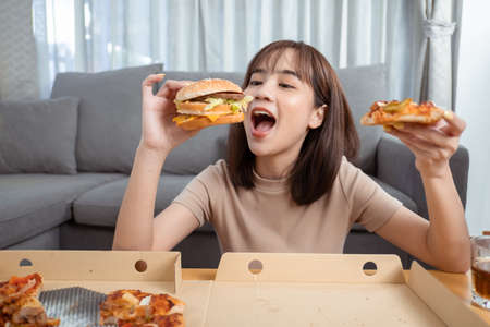 Close up asian woman takeaway eating junk food hamburger and pizza close-up shot in living room at home, Fast food delivery service safe and stop coronavirus spread by social distancing concept.