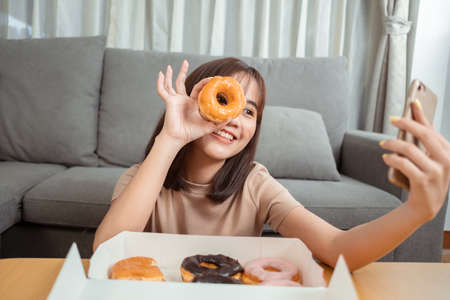 Young asian woman takeaway eating donut junk food enjoy to selfie update on social in living room at home, Fast food delivery service safe and stop coronavirus spread by social distancing concept.