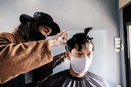 Asia Barber Shop Hair cut queueing customer's wearing face mask prevention business reopening after covonarirus lockdown, Men's hairstyling and new normal lifestyle concept.