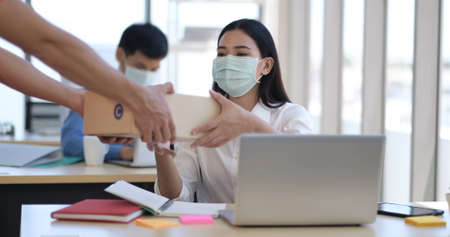 Young asian businesswoman in mask receiving a package from courier delivering to customer at work, smiling employee or happy worker accepting postal parcel at office.
