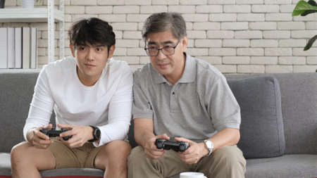 Asian two age generations men family old father embracing young adult son having fun enjoying play video game funny video using at home sit on sofa. Happiness Asian family concepts.
