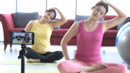 Young asian couple in sportswear recording video blog or vlog about healthy lifestyle on camera while doing yoga at home. Two cute females making vlog about yoga and Healthy lifestyle. Zdjęcie Seryjne