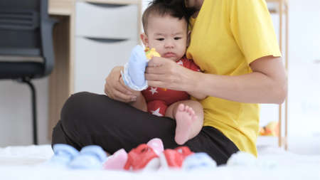 Young asian mother and baby overjoyed two playing with toys while Mother wearing funny home slippers to little daughter sitting on a carpet in the living room. Happy family having fun at home.