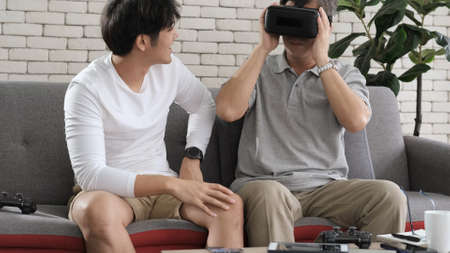 Asian two age generations men family old father playing video games virtual reality glasses. Young adult son having fun enjoying looking him father play video game funny video using at home. Zdjęcie Seryjne