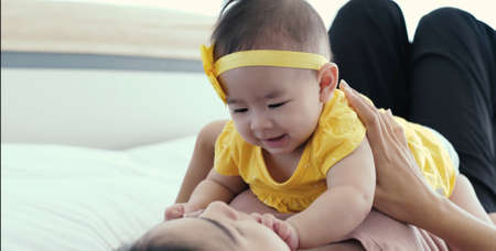 Asian mother in diaper playing with her's baby on bed in bedroom, Family having fun together, Young mother cuddling baby woman and new born relax breast feeding baby concept.