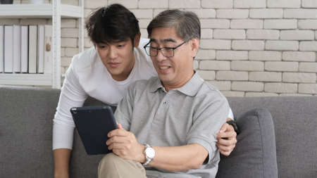 Asian father and son waving hands looking at camera, make video call with digital tablet with family while sitting in the living room. Their are laughing relaxing with video chatting with his family. Zdjęcie Seryjne