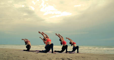 Group females yoga practice in class on mat stretching relaxation exercise with pose fitness sport for healthy on the beach and seaside at sunset relax holiday vacation time in summer. Zdjęcie Seryjne