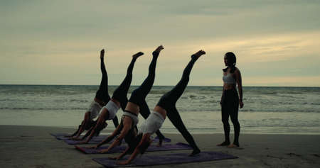 Group females yoga practice in class on mat stretching relaxation exercise with pose fitness sport for healthy on the beach and seaside at sunset relax holiday vacation time in summer.