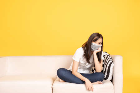Young asian woman wearing face mask resting on the sofa at over yellow background during coronavirus pandemic. Covid19 coronavirus epidemic virus symptoms.