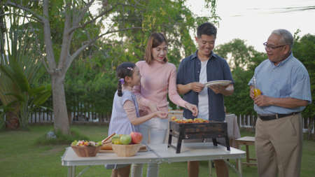 Asian female take BBQ food party summer grilling meat. Happy family enjoying meal together. People having outdoor party eating food at backyard home in garden.
