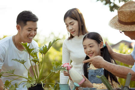 Asian couple with daughter gardening while watching laptop together in the backyard garden. Happy family gardening together and taking care of nature. People and ecology concept.