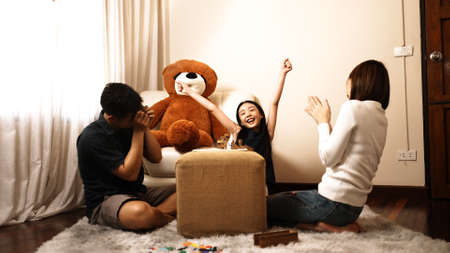 Happy asian family having fun with playing game wooden block at home with mother sit on floor together, family having fun enjoying talking with children. Reklamní fotografie