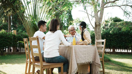 Happy asian family having festive dinner, Multi generation family enjoying meal together. People having outdoor party eating food at backyard home, lifestyle family concept party at summer garden. Reklamní fotografie