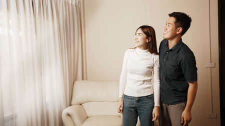 Portrait of two people, Asian man leading her into living room. Surprise in house with noel decoration indoors. Family Holidays Celebration.