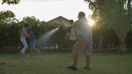 Happy asian senior grandpa pouring water from a hose. Funny family with his father playing with family having fun with spray of water in garden house in sunny backyard. Enjoy family holiday concept. Reklamní fotografie
