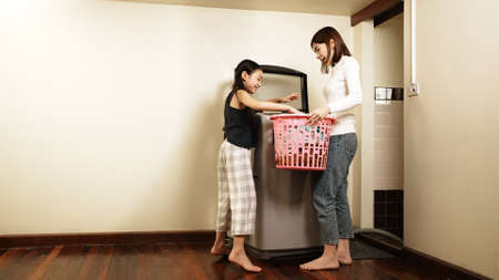 Asian little girl helping her mother to do laundry her loading clothes into a washing machine in a laundry room at home. Concept of love family and holiday at home. Household work concept.