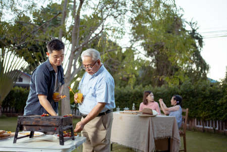 Happy asian family dining and tasting juice on glasses in barbecue dinner party, Multi generation family enjoying meal together. People having outdoor party eating food at backyard home in garden. Reklamní fotografie