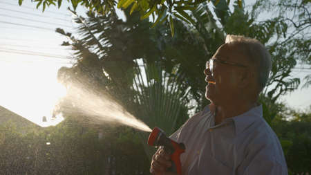 Happy asian senior grandpa pouring water from a hose. Funny Grandparent and grandkid playing with hose having fun with spray of water in garden hose in sunny backyard. Enjoy family holiday concept. Reklamní fotografie