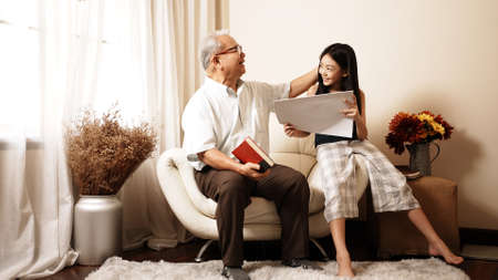 Asian handsome grandpa is holding a book while his granddaughter is drawing on a paper are smiling while spending time together sit on sofa in the living room at home. Enjoy family concept.