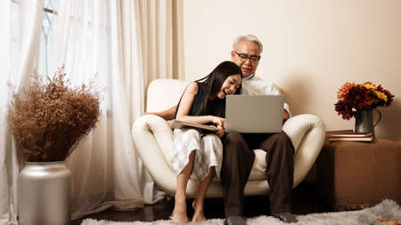 Asian handsome grandpa and granddaughter are using gadgets playing on device and smiling while spending time together sit on sofa in the living room at home. Enjoy family educational concept. Reklamní fotografie