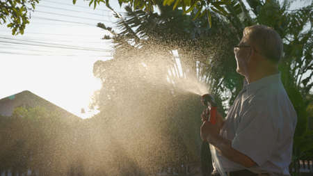 Happy asian senior grandpa pouring water from a hose. Funny Grandparent and grandchild playing with hose having fun with spray of water in garden house in sunny backyard. Enjoy family holiday concept. Reklamní fotografie