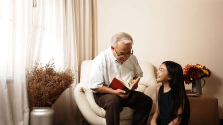 Asian grandfather reading book sit on sofa to granddaughter listening and sit on floor at home. Cheerful grandfather enjoy with family together at home. Family educational concept.