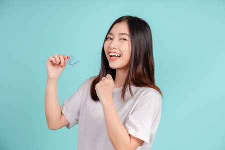 Dental Beautiful smiling of young asian woman with retainer braces glad emotion with white teeth increase confidence for healthy on blue background isolated, Happiness teenager facial expression.