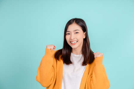 Dental of young asian woman wearing retainer braces glad emotion with white teeth increase confidence for healthy on blue background isolated, Happiness teenager smiling facial expression.