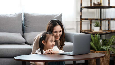 Happy family Mother and daughter watching videe entertainment with laptop computer technology the living room enjoy life at home concept. 版權商用圖片