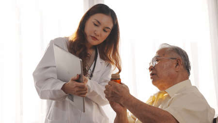 Asian female nurse tells how to take medicine to elderly senior grandfather patient at home medical visit, Elderly old male people healthcare support and encouraging the patient.