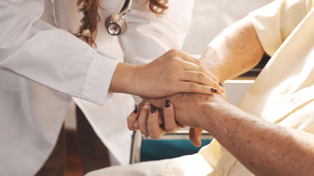 Close up Shot: Female nurse doctor in uniform holding hand senior grandfather patient at home medical visit, Elderly old male people healthcare support and encouraging the patient in life. 版權商用圖片