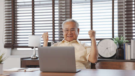 Happy Senior male using laptop searching for health insurance online website on laptop computer buying insurance fot retirement sitting at home, Elderly healthy lifestyle concept.
