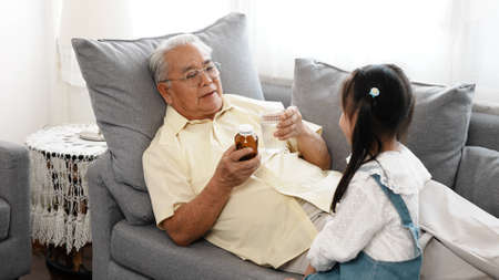 Happy family Little asian daughter carried a drug and glass of water to the sick grandfather on the sofa in the house take care, Elderly old man patient retired enjoy life concept.