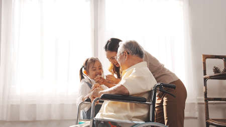 Happy Family Multi-generation Mother and daughter taking care of the senior granddfather in the house, sitting on the wheelchair happiness, Elderly retirement concept. 版權商用圖片