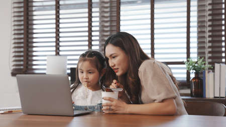Little asian daughter online education using laptop computer with mother feeding noodles in the living room at home, Happy family people lifestyle activities concept. 版權商用圖片