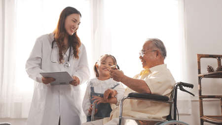 Asian female nurse tells how to take medicine to elderly senior grandfather patient at home medical visit, Elderly old male people healthcare support and encouraging the patient with granddaughter.
