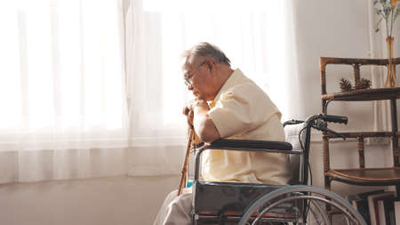 Elderly Senior male stay home after retirement alone at home unhappily and lonely his looking out the window with wheelchair and cane. Standard-Bild