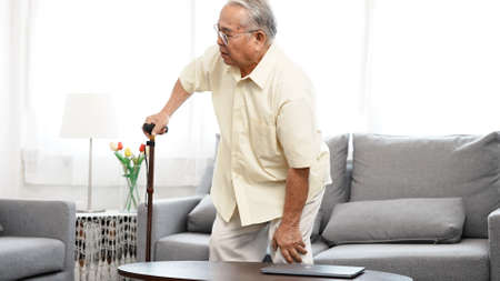Asian Eldery senior man feeling pain in knee and standing up step walking the floor with a cane at home in living room alone. Learn how to be alone after retirement concept.